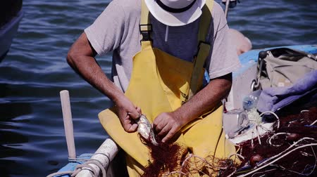 fishermen : a fisherman with a white hat working on a fishing net on his boat Stock Footage