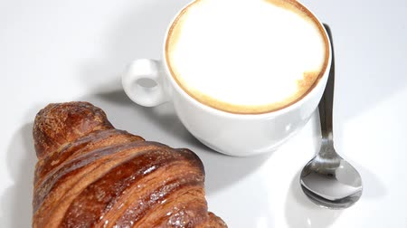 kahvehane : Croissant and cappuccino on a white plate rotating.