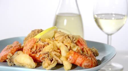 kalmar : Mixed fried fish rotating over white. A bottle and a glass of wine on background Dostupné videozáznamy