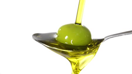olivový olej : Olive oil poured on a spoon over white background