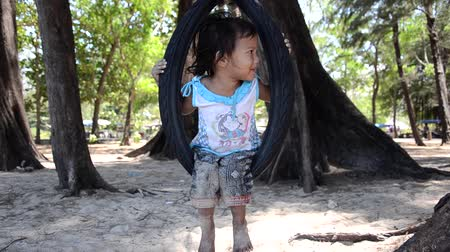 bída : thai child on a tire swing