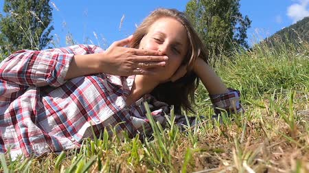 darbe : young woman lying in a grass blows a kiss toward the camera
