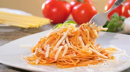 традиционный : Traditional italian recipe. Eating spaghetti with tomato sauce, parmesan cheese and basil. Стоковые видеозаписи