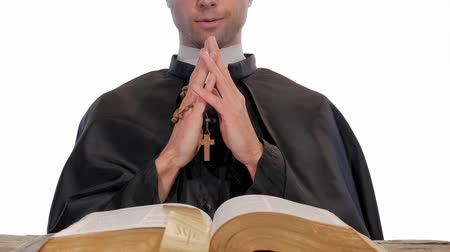 clerical : conceptual portrait of praying priest with wooden rosary reading Holy Bible