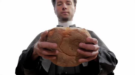 cassock : clergyman breaks bread as in the Gospel parable