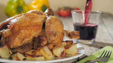 tavuk : a table spread with roast chicken, baked potatoes, fresh vegetables and pouring red wine
