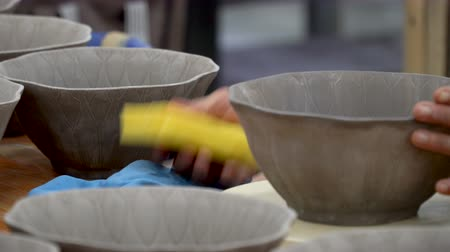 turn table : traditional pottery making, close up of potters hands shaping a bowl