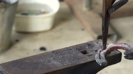 The blacksmith kicks a horseshoe close up