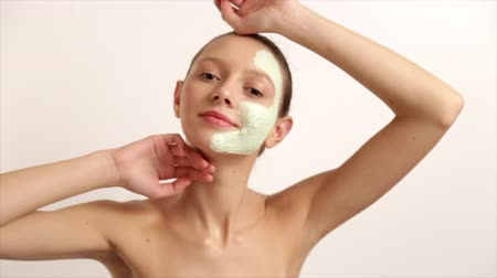 The Young Beautiful Girl Has Caused A Cosmetic Mask, White Face Cream Skin Health, Stands On A Light Background Prores Codec Dostupné videozáznamy