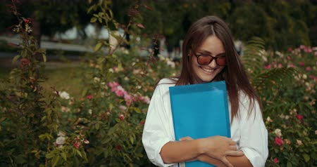 Beautiful Fashionable Stylish Young Girl In Sunglasses At The Park On Vacation On A Sunny Day Wih A Folder Stockvideo