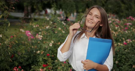 Business Woman Controls The Execution Of Works. Young Attractive Girl In Sunglasses In White Shirt Against Flowers Background Removes The Sunglasses And Look Dazzlingly. Slow Motion Prores Codec Dostupné videozáznamy