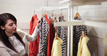 Sale, Fashion, Consumerism And People Concept - Happy Young Woman Choosing Clothes In Mall Or Clothing Store Dostupné videozáznamy