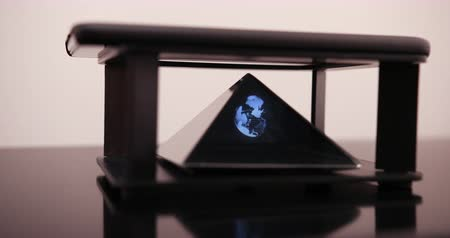Business, globalisering en toekomstig technologieconcept - close-up van zakenmanhand met transparante smartphone en aardehologram over zwart Stockvideo