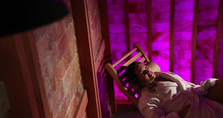 A Woman Lays On A Wooden Lounger In A Salt Sauna At An Expensive Hotel. Pink Wall. Therapeutic Sauna, Therapy, Medicine. Medium Shot. Prores Slow Motion Dostupné videozáznamy