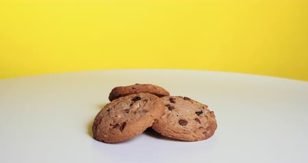 American Style Cookies With Chocolate Chips And Raisins Spin On A White Table On A Yellow Background. Prores Dostupné videozáznamy