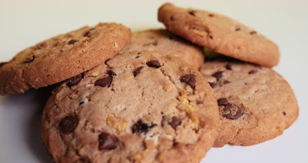 American Style Cookies With Chocolate Chips And Raisins Spin On A White Table On A Yellow Background. Close Up. Prores