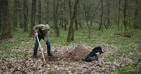 Bloody Murderer Is Digging A Grave For The Victim. The Guy Digs A Hole In The Woods. Criminal Concept. A Man Wants To Bury Stolen Things In The Woods. Prores, Slow Motion