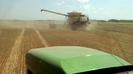 összeg : Harvester Collects Crop, Tractor Goes To Combined View From Cabin Of Tractor. Summer Heat During Harvest. At Distance There Is Small Amount Of Dust From Wheat Collection And Rye. Prores, Slow Motion Stock mozgókép