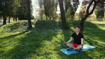 position du lotus : Young Man Practicing Yoga Outdoors At Park Sitting On Mat In Lotus Pose Closed Eyes Meditating. Prores, Slow Motion, 4k