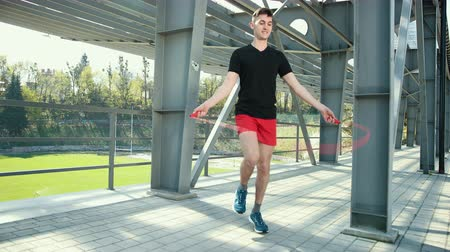 skákání : Portrait Of Fit Young Man With Jump Rope On Platform Near Metal Racks. Fitness Skipping Workout Outdoors. Guy Jumps Near Metal Pillars In Background Of Stadium. Dressed In Black T-Shirt And Red Shorts