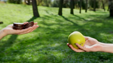szál : Hands choose what eats a green apple or chocolate bake. In the background there is a park, sunny weather. The concept of organic nutrition and healthy lifestyle. Prores, Slow Motion, 4k
