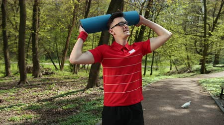health insurance : A young man puts a yoga mat on his head and smiles at the camera. Dressed in a red t-shirt. Summer sunny weather in the park. Concept of a healthy way of life and rest. Prores, Slow Motion, 4k Stock Footage