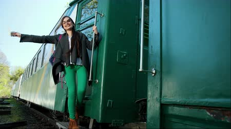nazomer : A very beautiful young girl standing on the train carriage stairs smiles and waves a ticket that holds in her hand. Concept of travel and active rest. Farewell to your beloved person before the trip Stockvideo