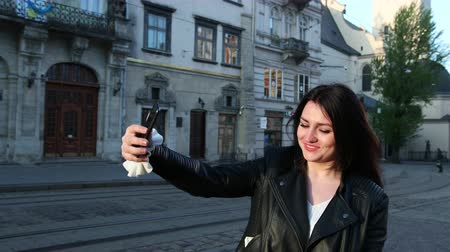 make photo : Beautiful brunette woman looks at her phone and takes selfies in city. Behind good urban architecture. A blogger blog leads live on the phone. Prores, Slow Motion, 4k