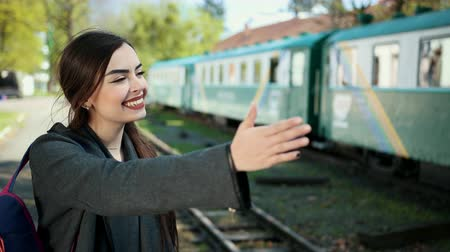 оставлять : One beautiful and happy girl standing in front of the train carriage holds a ticket in her hands and says goodbye to her beloved person and relatives before leaving. On her shoulder is a backpack. Стоковые видеозаписи