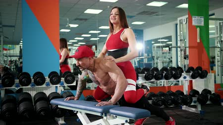 improve : Athletic man in red cap on his head pushes his seat off, increasing his muscles. Sports activities in gym, concept of healthy lifestyle. On back, the guy is sitting in a beautiful girl in a red suit.