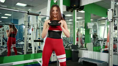 javul : A beautiful girl in a red suit holds the metal disk with two hands at the neck level and squats with it. The woman is engaged in the hall. The concept of sport and healthy lifestyle, bodybuilding Stock mozgókép