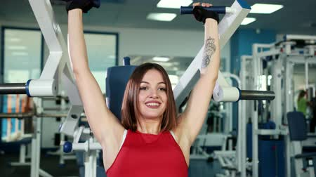 seksualiteit : Beautiful girl in red sports suit doing exercises on device, increasing biceps on her hands. Concept of healthy lifestyle, workout in gym. the concept of sexuality and femininity and a excellent look