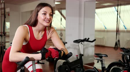 manken : Beautiful young woman with sexual ass twists bicycle pedals in gym. Dressed in red sports suit. And she leaned her hands on bicycle knobs. concert of healthy lifestyle. Close-up, Prores, Slow Motion Stok Video