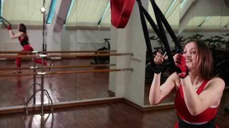 horizontal bar : A beautiful sexy girl is tightened on special ropes by taking a step back and forth into the gym. Dressed in red sport suit. Improves body and muscle flexibility Stock Footage
