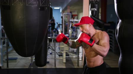 zuřivý : Handsome young man with a bare torso in a red cap and boxing gloves boxing on goal. Wide angle, Prores, Slow Motion