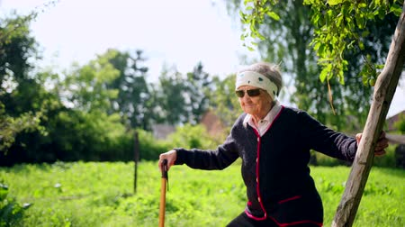 squatting : Very old woman doing outdoor sports. One hand holds the stick, other behind barrel and does exercises squatting, stretching. Yoga in yard on background of garden with trees. Slow motions, prores Stock Footage