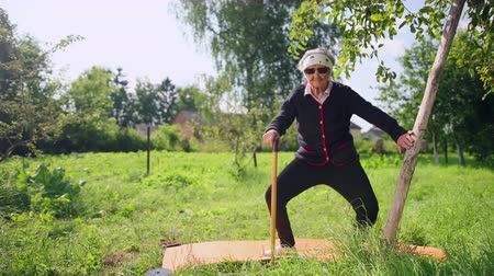 feroz : Very old woman doing outdoor sports. One hand holds the stick, other behind barrel and does exercises squatting, stretching. Yoga in yard on background of garden with trees. Slow motions, prores Vídeos