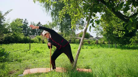 ohnutý : Very old woman in sunglasses holds her hand at stick and perform physical exercises leaning in different directions and stretching. Located on carpet and doing physical education. Health and longevity Dostupné videozáznamy