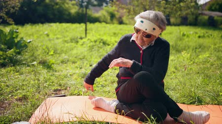 ohnutý : Aged lady in sunglasses on mat for yoga puts foot to foot and makes stretch housings. 100 years old woman. Woman is doing on a mat for exercises. Behind the green trees and beautiful summer landscape