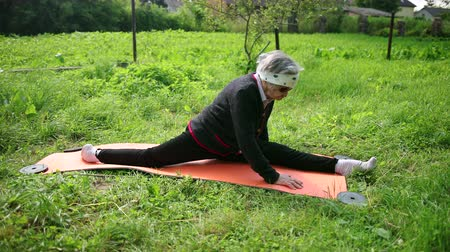 čelo : A pensioner woman sits on a twine in sunglasses on a yoga mat and touches her forehead to her leg, showing flexibility.