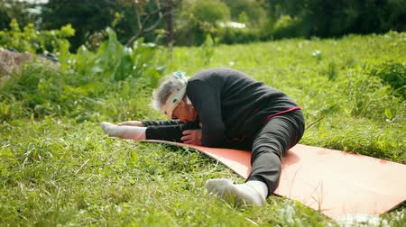 絶滅寸前の : A long-lived woman is engaged in yoga sitting on a carpet. In sunglasses, she spread his legs wide and leaned to the knees with his head to the left, to the right. Wide angle, prores, slow motion