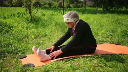 strong granny : 100 year old athlete woman lays on a yoga mat in sunglasses and leans, bending to the toes with his hands and head, increasing the flexibility of the body. oncept of health and endurance and positive