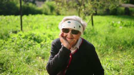 donaciones : Portrait of an old woman of a long-life who is 100 years old. She sits in sunglasses, looks at the camera, smiles, holds her head in her hand. Behind the garden with green trees. Summer, sunny hot day