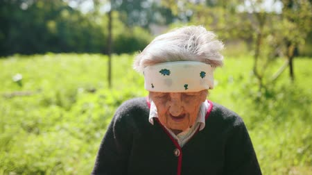 donaciones : Portrait of tired blind woman who sees badly in his eyes, squint, is tired, sick, frustrated from life. Dressed in black sweater, against background of green grass and trees of court. Sunny summer day Archivo de Video