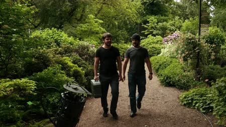 trepadeira : Two male hooligans go to the front and start running to the camera around beautiful trees and greenery shrubs in the botanical garden of Wroclaw, Poland