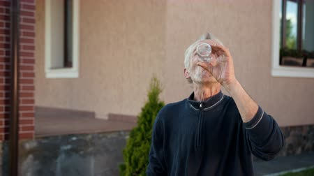 without face : an old man, gray-haired, wincing, drinking from a clear glass bottle, closing his eyes, happy, exhales, enjoys, wipes his face, a day near the house, slow shooting Stock Footage