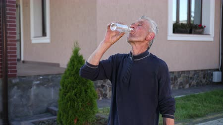 rebuliço : old man, gray-haired, drinking from a transparent glass bottle, happy, exhales, enjoys, wipes his face, the day near the house, closes the bottle, eating fruit, slow shooting