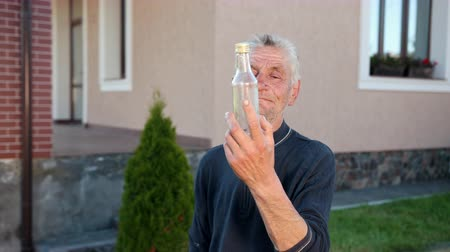 without face : an old man, gray-haired, in a blue sweater, drunk, holding and looking at a glass transparent bottle, smiling and kissing her, near the house, in the afternoon, slow shooting