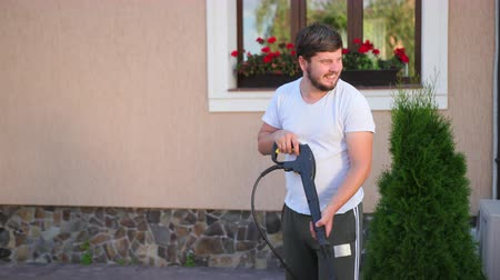 resistente : a young person with a beard, in a white t-shirt, smiling cleans near a beautiful house, washes the sidewalk, washes with high pressure water jets, in the afternoon, slow shooting, the camera goes down