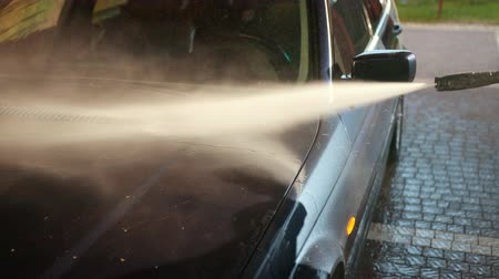 externo : a man, a worker, washing a dark car. wash using high pressure water jet. the spray flies in all directions. day. close-up, slow motion Vídeos